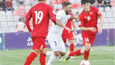 اللاعب منذر أبو عمارة يمر بالكرة بين لاعبي فيتنام خلال التصفيات الأسيوية السابقة - (الغد)