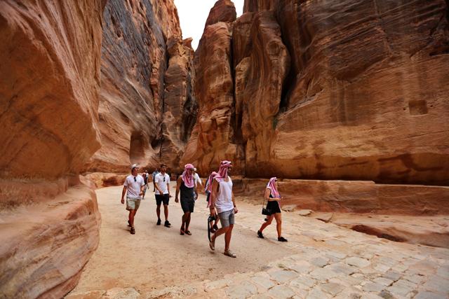 سياح يسيرون في السيق بمدينة البتراء الأثرية-(ارشيفية)