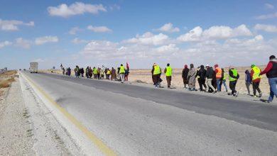 متعطلون عن العمل يسيرون على الطريق الصحراوي باتجاه عمان-(من المصدر)