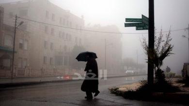مواطن يتقي سقوط المطر بمظلة في أحد شوارع عمان -(الغد/ أرشيفية)