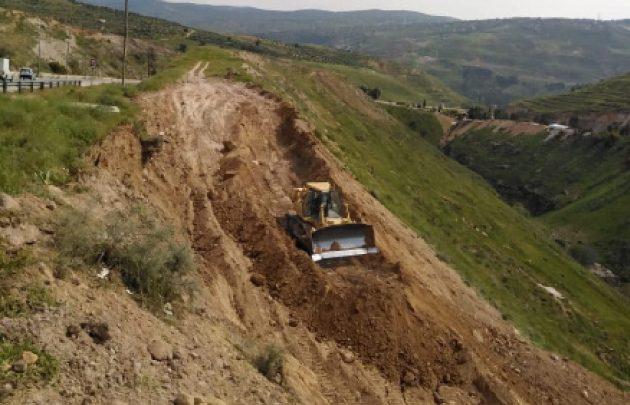 آلية تعمل في موقع الانهيار على طريق إربد عمان قرب جامعة جرش-(الغد)