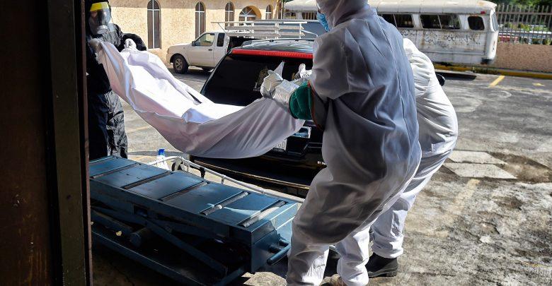 عمّال ينقلون من جثة أحد ضحايا كوفيد-19 المشتبه فيهم في سان إيسيدرو بانثيون في أزكابوتزيالكو، مدينة المكسيك، في 10 يونيو، 2020 . / أ ف ب